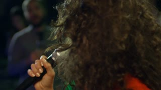 Close up face of cheerful curly haired young woman using microphone when singing karaoke at party in nightclub