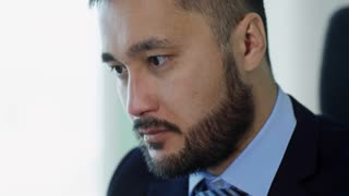 Close up face of concentrated Asian man working with laptop computer when sitting at desk in office
