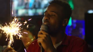 Close up face of ecstatic black man holding sparkler firework and dancing when singing into microphone in karaoke bar at party with friends