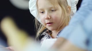Close up face of interested girl in chef hat smiling when watching unrecognizable man roll out dough
