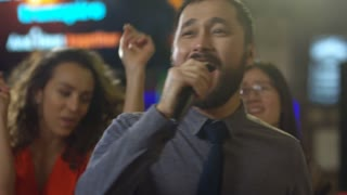 Close up face of joyous Asian man singing into microphone when enjoying music with group of multi ethnic friends on dance floor in karaoke bar