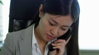 Close up face of young Asian businesswoman having phone conversation when working in office