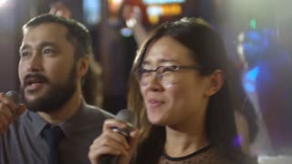 Close up face of young Asian woman in glasses singing into microphone together with male friend when partying in karaoke bar
