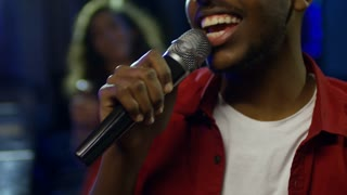 Close up face of young black man following song lyrics on screen when singing karaoke with microphone at party in nightclub