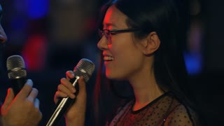 Close up faces of two smiling Asian people looking at each other and singing into microphone in karaoke club
