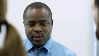 Close-up of african american businessman in blue formal shirt discussing something with coworkers in the office