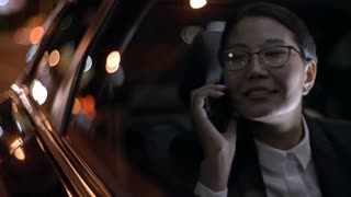 Close up of Asian businesswoman in glasses and suit chatting on mobile phone and looking out window of moving car at night