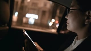 Close up of Asian businesswoman in glasses and suit sitting in backseat of moving car and browsing social media on mobile phone