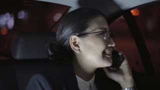 Close up of cheerful Asian businesswoman in glasses and suit sitting in backseat of moving car and chatting on mobile phone