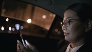 Close up of cheerful Asian businesswoman in glasses and suit smiling and looking at mobile phone while riding in backseat of taxi driving through city at night