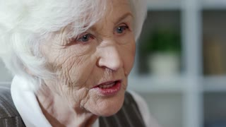 Close up of face of confident senior woman with grey hair having conversation with person off camera