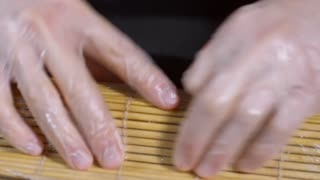 Close up of gloved hands of unrecognizable cook wrapping sushi with bamboo mat