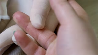 Close up of hands of unrecognizable nurse wiping finger of patient with antiseptic, then using lancing device to draw blood for glucose testing