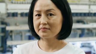 Close-up of mid-aged asian woman looking at camera while textile machine processing fabric in background