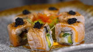 Close up of tasty Philadelphia sushi rolls with black caviar on top lying on spinning plate