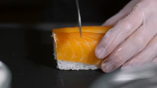Close up of unrecognizable cook in gloves cutting Philadelphia sushi rolls with knife