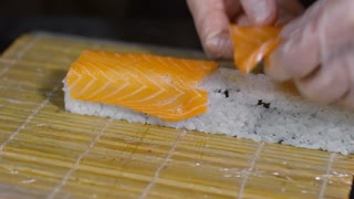 Close up of unrecognizable cook in gloves putting slices of salmon on sushi, then wrapping it with bamboo mat