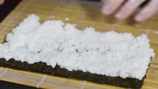 Close up of unrecognizable cook in gloves wrapping nori seaweed and rice into bamboo mat and pressing down to make rolls
