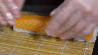 Close up of unrecognizable cook wearing gloves wrapping sushi with bamboo mat and forming rolls