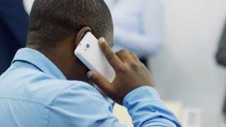 Close-up rear view of African American businessman in formal shirt talking on smartphone at work