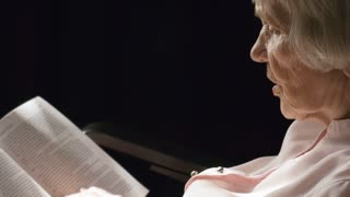 Close up shot of concentrated elderly woman sitting in chair on black background and reading storybook aloud