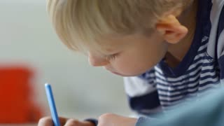 Close up shot of cute little boy sitting on the floor and drawing something with blue felt-tip pen