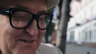 Close up shot of elderly man in glasses eating ice cream outdoors and smiling