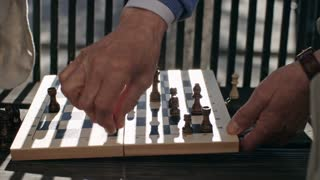 Close up shot of elderly man sitting on bench in park and playing chess with his friend, tilt up