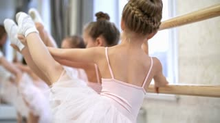 Close up shot of little girls stretching legs at ballet barre, one of them getting distracted and picking her nose, rear view