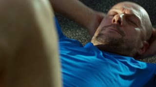 Close up shot of mature man doing twist crunches on the floor at the gym