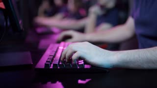 Close-up shot of unrecognizable male hands using keyboard to play computer game in cybersport competition