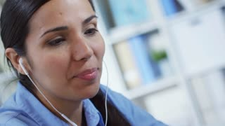 Close up shot of young Hispanic woman in headphones working at the office and using smartphone for video communication with colleague or friend