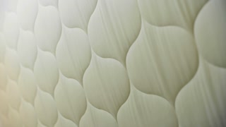 Close-up view of quilted white cotton fabric during process of manufacturing in textile factory