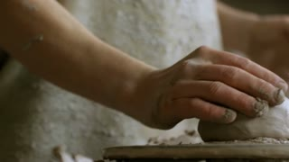 Close up with PAN of hands of unrecognizable male artisan putting piece of clay on pottery wheel and shaping it with wet hands
