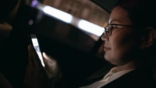 Close up with slowmo of Asian businesswoman in glasses and suit seating in backseat of taxi and browsing social media on mobile phone