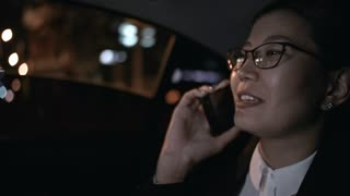 Close up with slowmo of happy Asian businesswoman in glasses smiling and talking on mobile phone while sitting in backseat of taxi driving through city at night