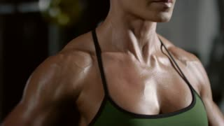 Closeup mid-section of sweaty muscular woman doing dumbbell lateral raise in gym