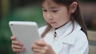 Closeup of adorable little Asian girl sitting outdoor and typing on touchscreen of digital tablet