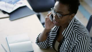 Closeup of african american business lady in eyeglasses sitting at desk in office with opened notepad and documents on it and speaking on mobile phone