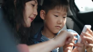 Closeup of Asian mother and little son sitting in car, talking and using smartphone together during ride