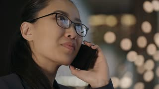 Closeup of beautiful Asian businesswoman in eyeglasses having phone conversation in hotel lobby