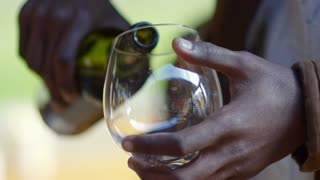 Closeup of hands of African man pouring red wine into the glass at outdoor party