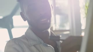 Closeup of young african american man writing business ideas on whiteboard and talking to colleague in the office at sunny day