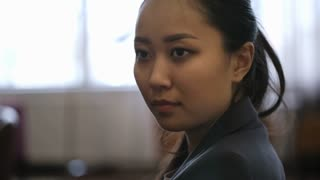 Closeup of young Asian businesswoman looking at something while sitting in hotel lobby