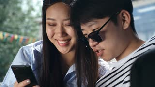 Closeup of young Asian woman and man smiling and watching video on smartphone outdoors at summer day
