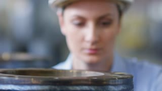Closeup shot of female engineer in hardhat checking quality of metal equipment. She looking and touching surface of metal pipe