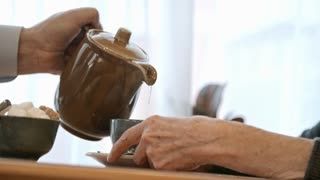 Closeup shot of hands of senior man pouring tea from pot into cup for elderly woman at cafe table