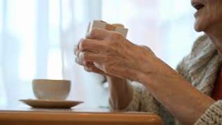 Closeup shot of hands of senior woman giving a gift box to man at cafe table with coffee cups on it