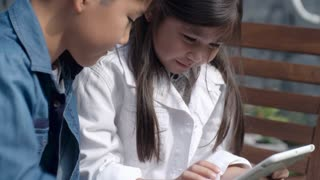 Closeup shot of little Asian girl learning how to use digital tablet with brother outdoors