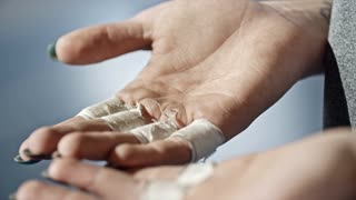 Closeup shot of woman with rough female hands with taped fingers clenching fists after weightlifting